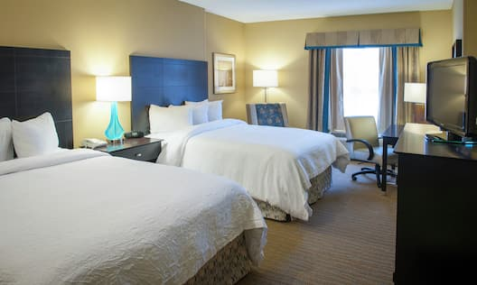 Guestroom with Two Queen Beds, Lounge Area, Work Desk, and Room Technology
