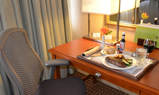 Detailed View of Room Service Tray With Steak, Meal, Beverages, Condiments, and Flower on Work Desk With Illuminated Lamp and Ergonomic Chair By Window With Drapes