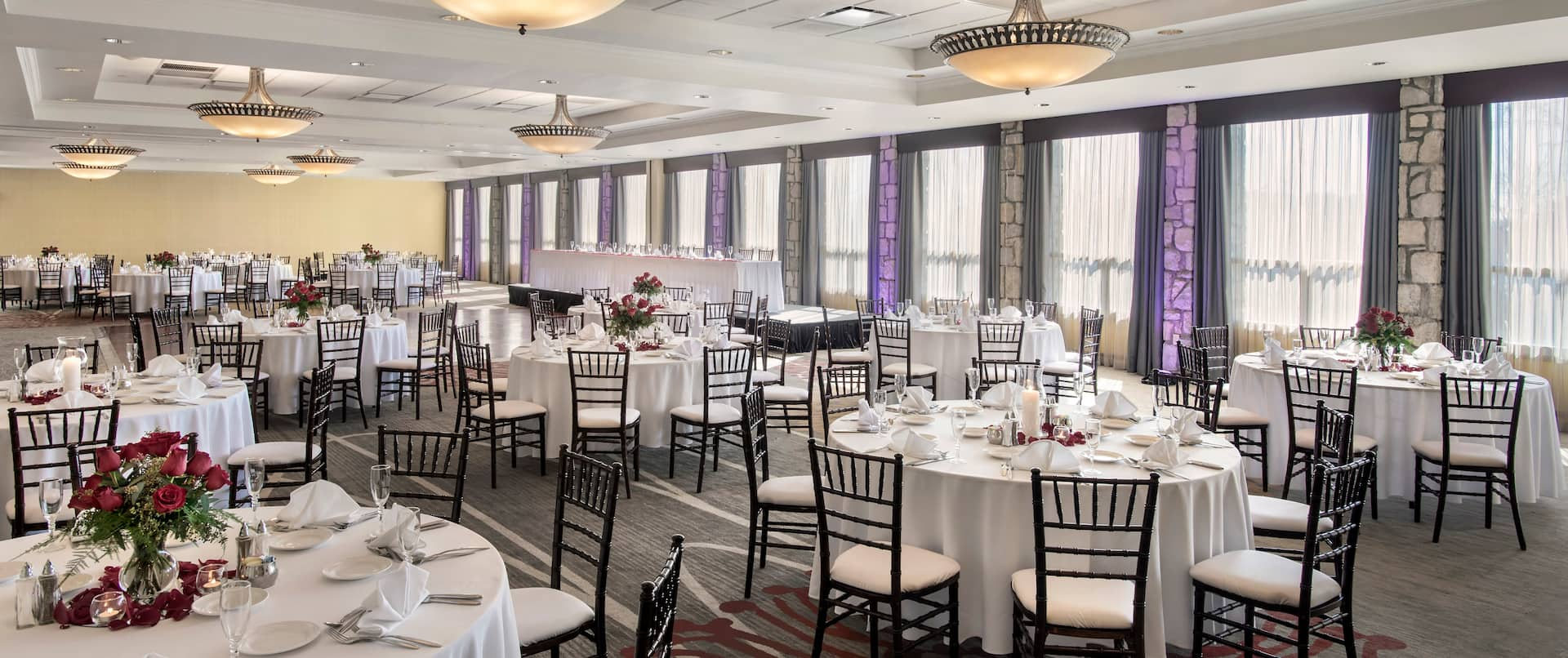 Place Settings, Red Roses, Candles, Drinking Glasses, Fan-Folded Napkins, and White Linens on Round Tables, Chairs, Head Table on Elevated Platform by Windows With Long Drapes in Ballroom Set Up for Wedding Reception
