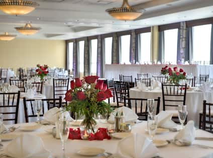 Place Settings, Red Roses, Candles, Drinking Glasses, Fan-Folded Napkins, and White Linens on Round Tables, Chairs, and Head Table by Windows With Long Drapes in Ballroom Set Up for Wedding Reception