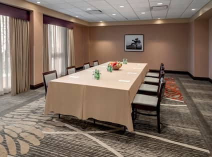 Meeting Room With Water Bottles, Fruit, Writing Utensils, and Seating for Eight at Table With Beige Linens, Wall Art, and Windows With Long Drapes