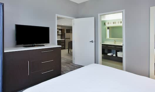 Guest Room with King sized Bed and TV and Partial View of Kitchen and Bathroom Areas