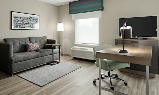 Guestroom Living Area with Sofa, Work Desk, and Television