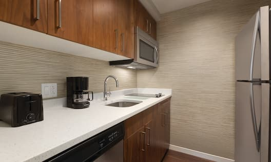 In-Suite Kitchen with toaster, coffee maker, and fridge