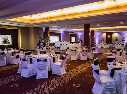 Banquet Tables With Place Settings, Flowers, Drinking Glasses, and White Linens, White Chairs With Black Sashes, Dance Floor, Two Head Tables, Three Presentation Screens, and Purple Lighting in Ballroom Set Up For Wedding