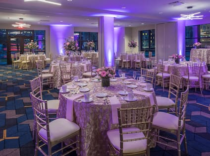 Ballroom With Purple Lighting, Place Settings, Flowers, Drinking Glasses, White Napkins, and Decorative Linens on Round Tables, Chairs, Windows and Glass Entry Doors