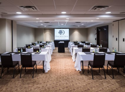 Classroom Setup in  Conference Room With White Linens on Tables, Chairs, Projector on Table With Black Linens, and Presentation Screen