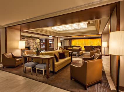 Tables, Illuminated Lamps, andsSoft Seating Around Fireplace in Lobby Lounge Area With View of Front Desk