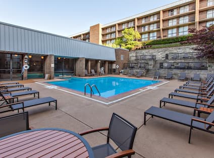 Daytime View of Tables, Chairs, Loungers, and Stairs Leading to Hotel Exterior by Indoor/Outdoor Pool