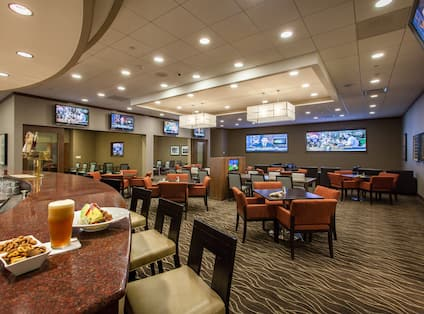 Tables, Chairs, TVs, and Counter Seating at Well-Stocked Bar at Champions Lounge