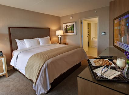 King Bed Between Two Illuminated Lamps on Bedside Tables, Wall Art, Open Doorway to View of Bathtub, TV by Room Service Tray of Cookies and Milk in Guest Room