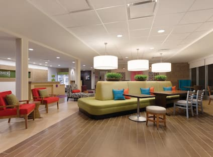 Lobby Lounge Area With Two Red Arm Chairs, Decorative Lighting Above Large Green Sofa, Tables, and Chairs With View of Front Desk and Snack Shop