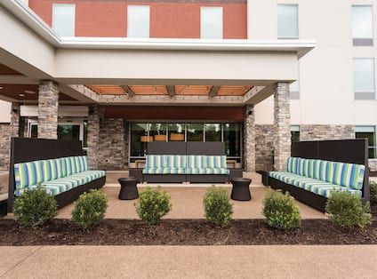 Daytime View of Outdoor Patio With Landscaping by Two Small Tables and Three Striped Sofas in Lounge Area