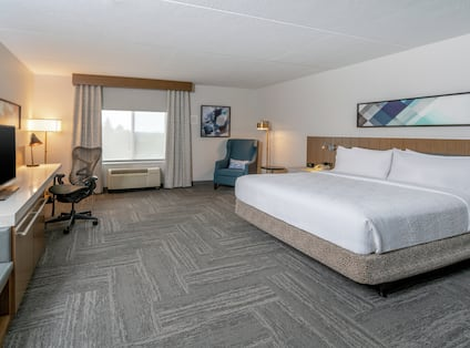 Mobility accessible king guest room with soft chair desk and tv