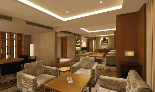 Tables, Chairs, Illuminated Lamps, Wall Art, and Soft Seating in Presidential Suite Living Area