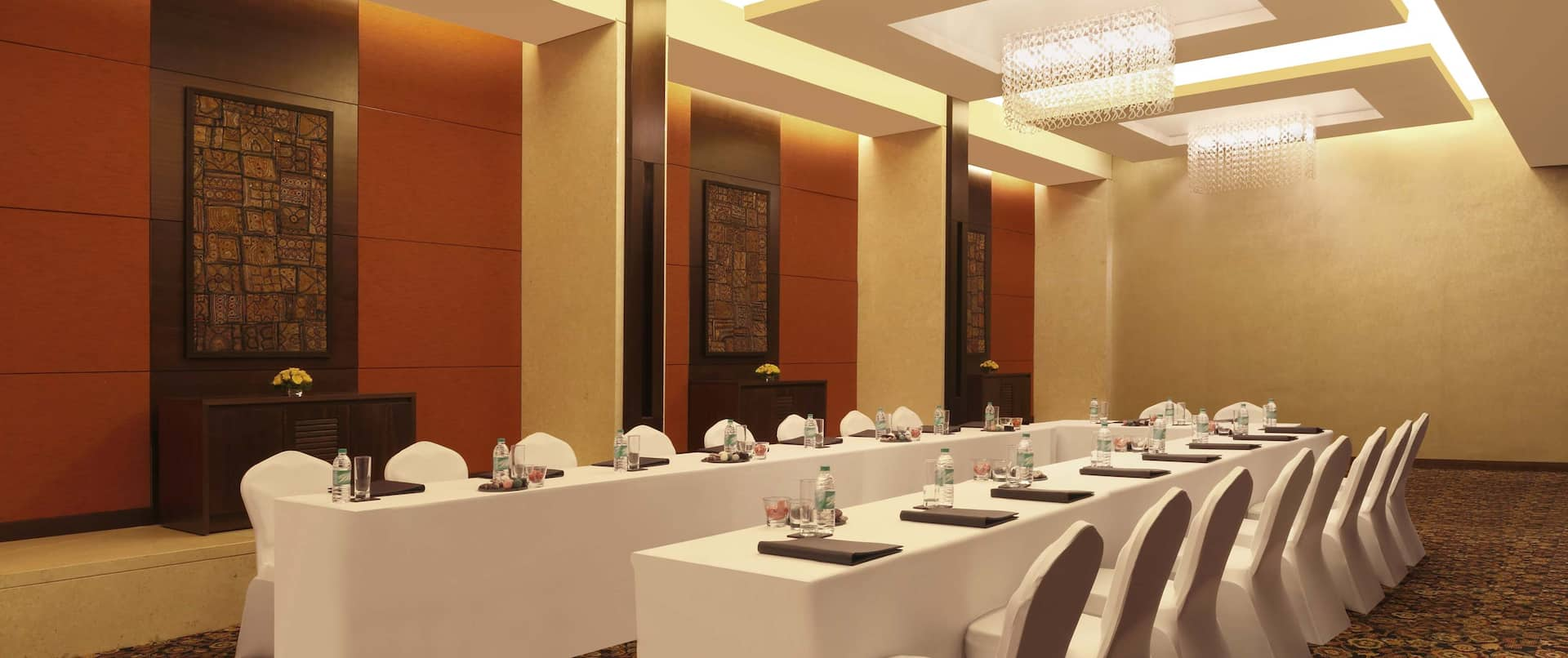 Vihara Banquet Hall With Wall Art, U-Shaped Table With Water Bottles, Notepads,  White Linens, and White Chairs
