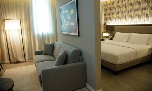 View of Junior Suite Bed and Separate Living Area with Sofa