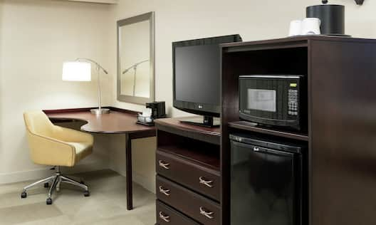 a work desk, tv, mini fridge and microwave in a guest room
