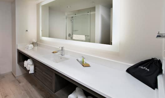 Sink/Vanity Under Mirror with Lights, Shower with Sliding Glass Doors, Towels, and Toiletries in Standard Bathroom