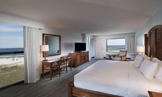 King Bed and Bedside Tables Facing Beach View, TV and Work Desk with Reading Chair in Corner by Window