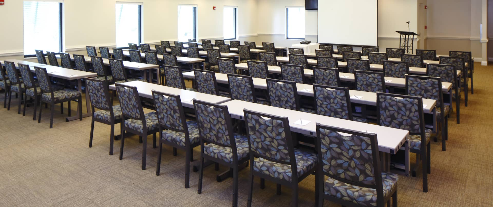 Classroom Setup in Meeting Room With Windows, Tables, Chairs, Presentation Screen, and Podium