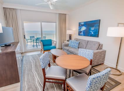 Junior suite living room with sofa, soft chair, coffee table, TV, small dining table with chairs, floor lamp, and balcony with gulf view