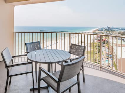 Junior suite balcony with lounge table, chairs, and gulf view