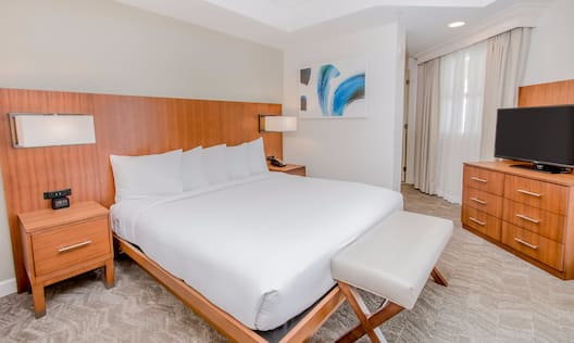 Suite with king bed, nightstands, lamps, footrest, and TV