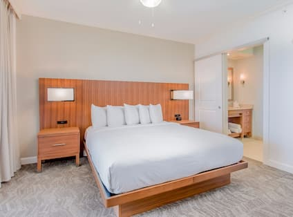 Suite with bed, nightstands, lamps, and partial view of bathroom
