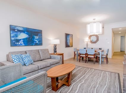 Suite living room with sofa, soft chair, coffee table, dining room with dining table and chairs, and room entrance