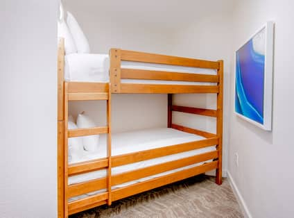 Junior suite with two queen bunk beds and art on the wall