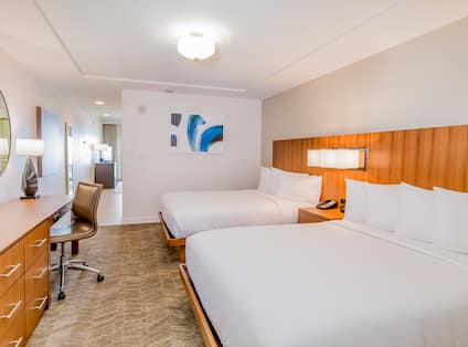 Junior suite with two queen beds, work desk, and TV