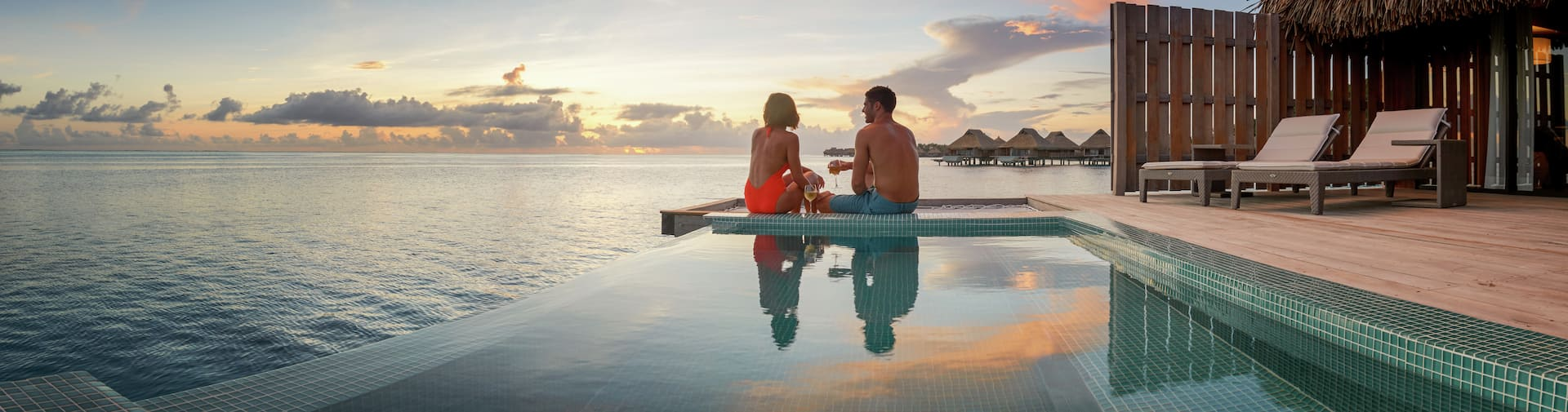 A couple perched on the edge of an infinity pool looking out to the ocean at sunset.
