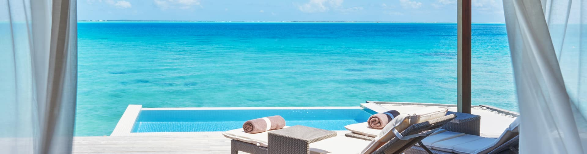 Two sun loungers overlooking crystal clear ocean