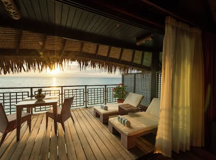 View of Overwater Bungalow Patio at Sunset