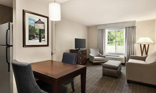 Spacious suite featuring lounge area with beautiful outside view, sofa, TV, and kitchen with dining table.