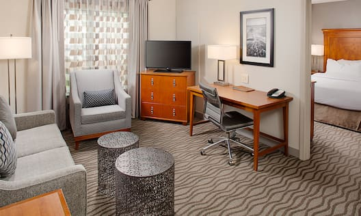 Suite with lounge sofa, chair, small coffee tables, TV, and work desk