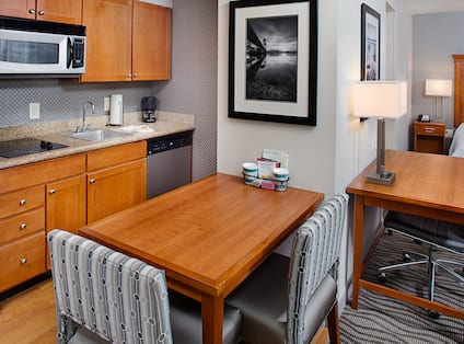 Suite with kitchen, dining table with chairs, work desk, and partial view of bed