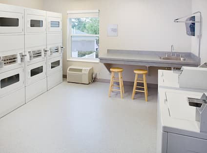 Laundry room with washers, dryers, and countertop with barstools