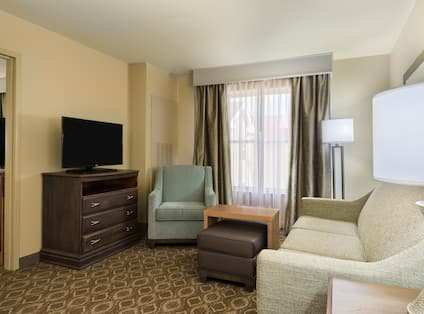 Suite living room with sofa, soft chair, coffee table, ottoman, and TV