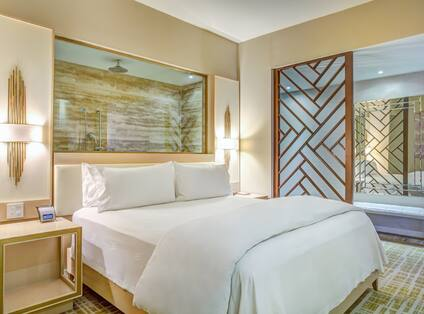 Suite with king bed, nightstands, lamps, and window showing walk-in shower above bed