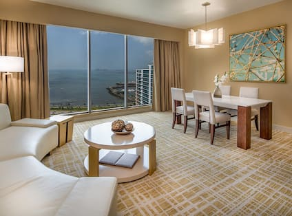 Panama Room living area, dining table with seating for four, and ocean view