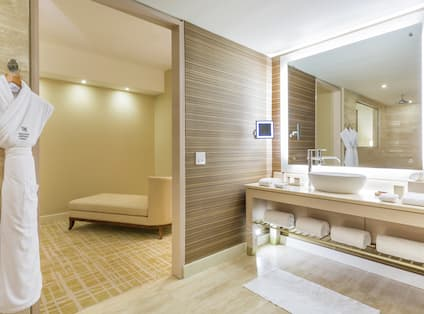 Bathroom Vanity Area with Amenities Large Mirror and Two Bathrobes