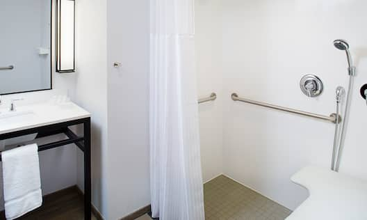 Vanity Mirror, Sink, Fresh Towels, Roll-In Shower With Shower Seat, Grab Bars, and Handheld Showerhead in Accessible Bathroom