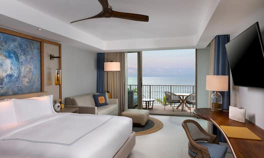 Guest Room with Large Bed Desk Sofa and Balcony with Ocean View