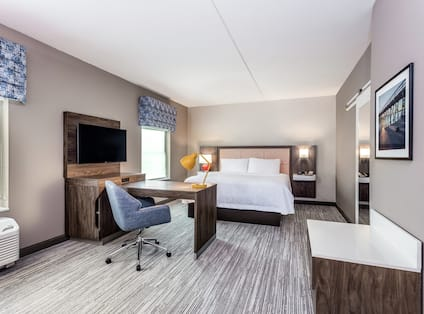 One King Bed Guest Suite with Wall Mounted TV and Work Desk