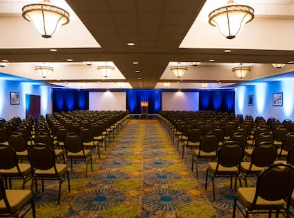 Ballroom in Theater Layout With Rows of Chairs Facing Two Projector Screens and Podium