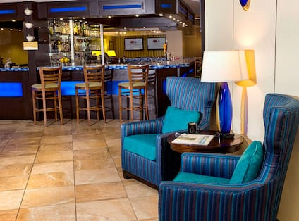 Table With Illuminated Lamp Between Two Blue Armchairs and Counter Seating at Well-Stocked Bar