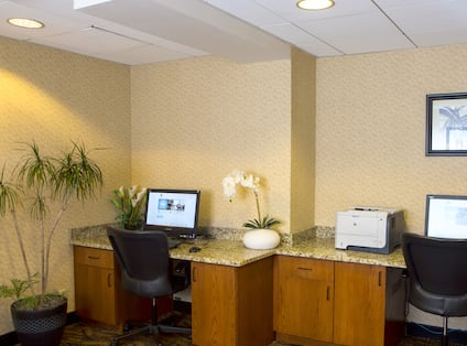 Business Center With Wall Art Above Two Computer Workstations, Ergonomic Chairs, and Printer