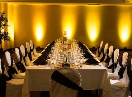 Large Table With White Linens, Black Napkins, Place Settings, and White Chairs With Black Sashes in Dramatically Lit Reception Room